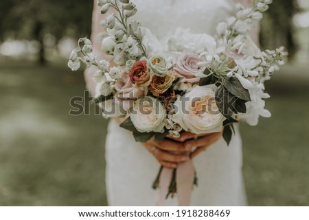 Bridal bouquet with white English roses held by a bride in white dress on green blur background Royalty-Free Stock Photo #1918288469
