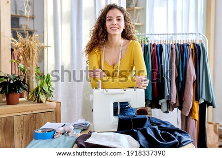 female designer of clothes standing by sewing machine in atelier, attractive tailor after work stand posing, looking at camera smiling. female use measuring tape for sewing and making garments Royalty-Free Stock Photo #1918337390
