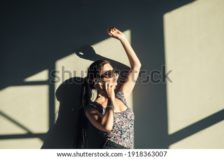 Portrait of a beautiful young woman calling by phone door.Sexy girl in short shorts talking on a smartphone.