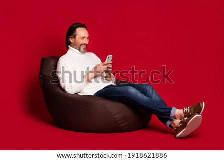 Full size profile portrait of handsome person sit soft chair funny blog post comment isolated on dark red color background