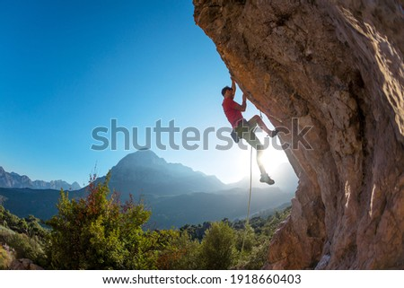 Athletic man climbs an overhanging rock with rope, lead climbing. silhouette of a rock climber on a mountain background. outdoor sports and recreation Royalty-Free Stock Photo #1918660403