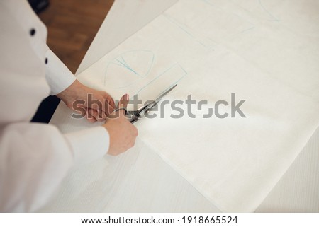 Close up. hands woman Tailor working cutting a roll of fabric on which she has marked out the pattern of the garment she is making with tailors chalk. Royalty-Free Stock Photo #1918665524