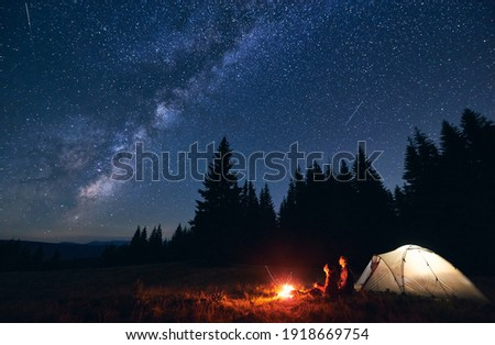 Young couple hikers sitting near bright burning bonfire and illuminated tourist tent, enjoying camping night together under dark sky full of shiny stars and bright Milky Way, warm summer evening. Royalty-Free Stock Photo #1918669754