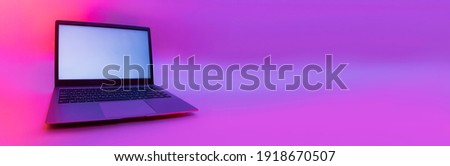 Slim modern laptop with white screen on the background creative light. Mockup in colorful bright neon UV blue and purple lights Royalty-Free Stock Photo #1918670507