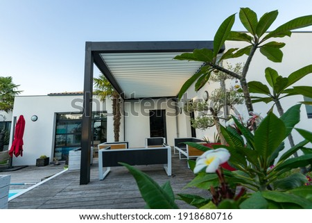 Trendy outdoor patio pergola shade structure, awning and patio roof, garden lounge, chairs, metal grill surrounded by landscaping Royalty-Free Stock Photo #1918680716