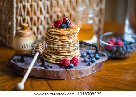 "Delicious pancakes with honey, blueberries and raspberries. Next to it is a wooden barrel with an inscription in Russian: ""honey"". The concept of the Maslenitsa holiday. Royalty-Free Stock Photo #1918708925"