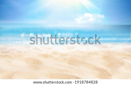 Natural blurred defocused background for concept summer vacation. Nature of tropical summer beach with rays of sunlight. Light sand beach, ocean water sparkles against blue sky. Royalty-Free Stock Photo #1918784828