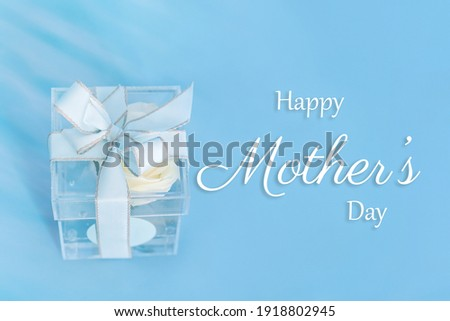 Glass transparent container wrapped in a bow with a white rose inside. Photo caption happy mathers day.