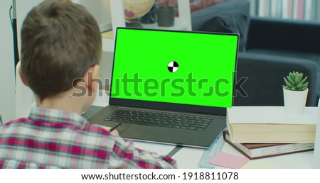 Little boy uses green screen chroma key laptop for learning, writes down useful information. Distance Learning, e-education, e-Learning, homeschooling concept.