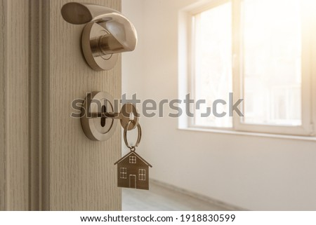 Open door to a new home with key and home shaped keychain. Mortgage, investment, real estate, property and new home concept Royalty-Free Stock Photo #1918830599