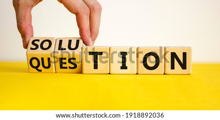 Question and solution symbol. Businessman turns wooden cubes and changes the word 'question' to 'solution'. Beautiful yellow table, white background, copy space. Business question and solution concept