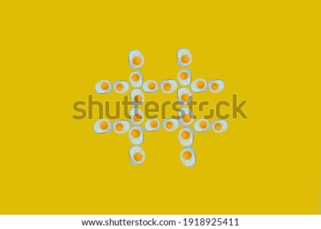 Hashtag icon made of fried eggs, food font concept. A unique collection of letters. Creative idea for spring, summer, autumn and winter. On a yellow background.