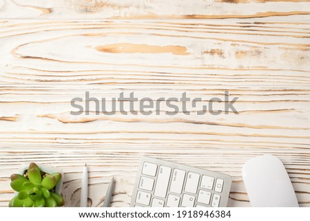 Overhead above close up view photo picture of computer keyboard mouse succulent and two pens isolated white wooden backdrop with empty space