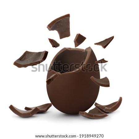 Broken milk chocolate egg on white background Royalty-Free Stock Photo #1918949270