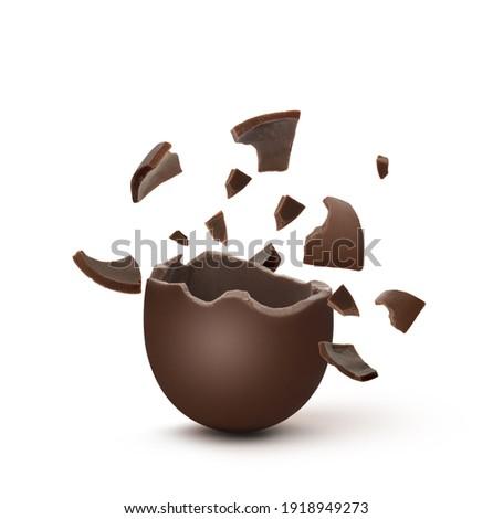 Broken milk chocolate egg on white background Royalty-Free Stock Photo #1918949273