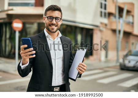 Young hispanic businessman smiling happy using smartphone at the city. Royalty-Free Stock Photo #1918992500