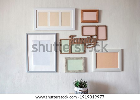 White wall with set of different empty vertical and horizontal picture frames to create family photo gallery on the wall, to capture a moment, mockup template on the white background, lifestyle