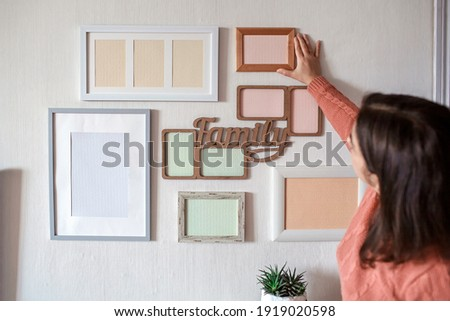 Girl hanging frame on white wall with set of different empty vertical and horizontal picture frames to create family photo gallery, to capture a moment, mockup template on white background, lifestyle