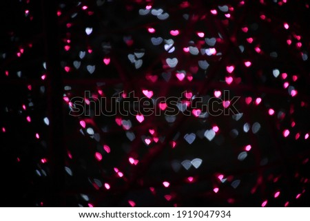 blur bokeh hearts shape pink and white with dark background