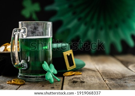 St. Patricks day concept - green beer and symbols, rustic background. Part invitation.
