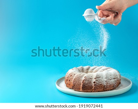 Woman's hand sprinkling icing sugar over fresh home made bundt cake. Powder sugar falls on fresh perfect bunt cake over blue background. Copy space for text. Ideas and recipes for breakfast or dessert
