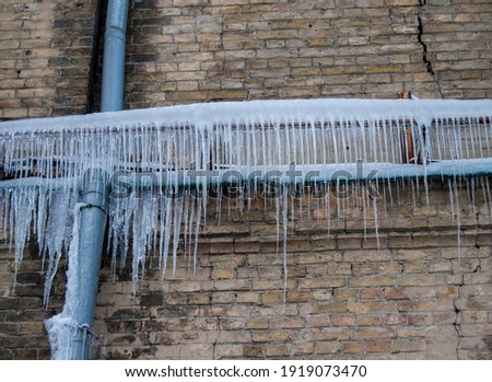 Thin icicles on the old crack brick wall.Drain pipe. Royalty-Free Stock Photo #1919073470