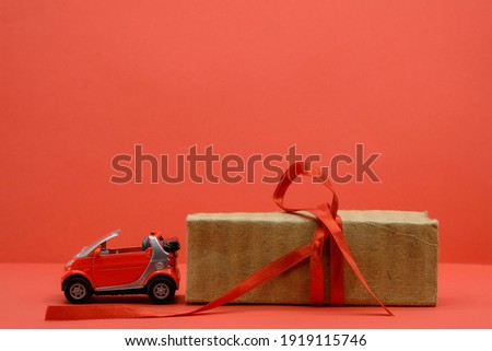 Red small car toy near the unpacked box with a red ribbon. Red background. Gift, surprise concept. Buy car concept. Copy space. Royalty-Free Stock Photo #1919115746