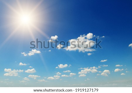 Strong sun, blue sky and cumulus clouds. Royalty-Free Stock Photo #1919127179