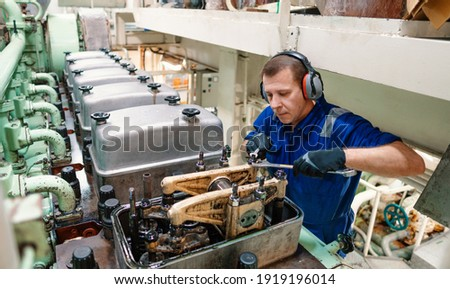 Marine engineer officer reparing vessel engines and propulsion in engine control room ECR. Ship onboard maintenance Royalty-Free Stock Photo #1919196014