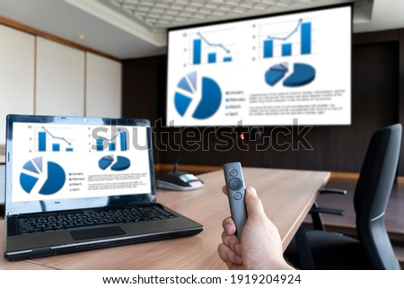 Close up hand holding a remote control slide presentation with presentation meeting on laptop and srceen in meeting room.