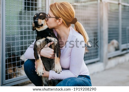 Young adult woman holding adorable dog in animal shelter. Royalty-Free Stock Photo #1919208290