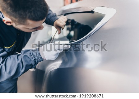 Car wrapping specialist putting vinyl foil or film on car. Selective focus.  Royalty-Free Stock Photo #1919208671