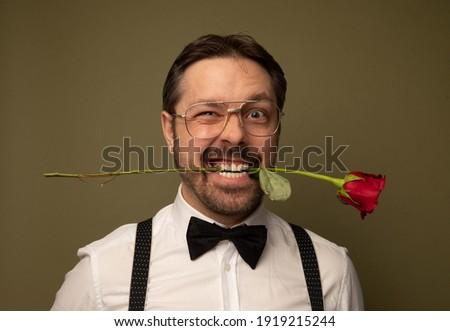 Studio portrait of a nerdy caucasian man holding a red rose in his mouth. He is dressed up and the background is green.