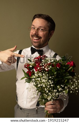 Studio portrait of a nerdy caucasian man holding a dozen of red rose . He is dressed up and the background is green.