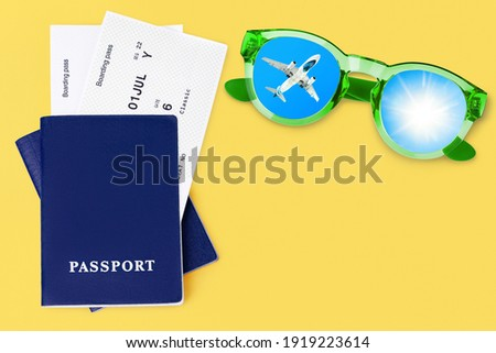 Two blue passports, boarding pass, flight ticket, sunglasses, airplane, sun, blue sky, top view close up, yellow background, summer holidays, vacation, travel banner, international tourism, copy space