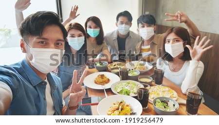 asian young six friends wearing face mask taking selfie in restaurant happily