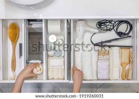 Top view of woman hands neatly organizing bathroom amenities and toiletries in drawer or cupboard in bathroom. Concept of tidying up a bathroom storage by using Marie Kondo's method. Royalty-Free Stock Photo #1919260031