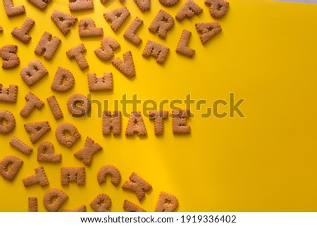 Word Hate in the middle of the picture made of tasty crunchy cookies in the form of English alphabet letters, textured bright yellow background, health, dieting and medical concept. Copy space