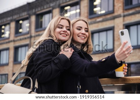 Two cute funny blonde girls makes selfie on their phone. They wear dark warm coats. Cold moody evening in european city