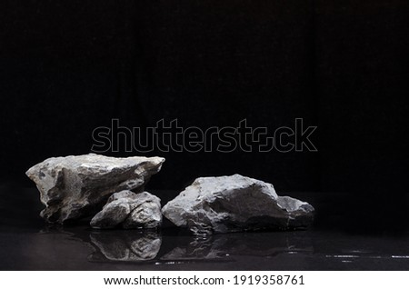 Luxury natural stone podium with water as shore at night for showing packaging and product on black background. Royalty-Free Stock Photo #1919358761