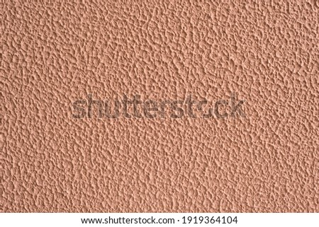 Background image of a wall with beige stucco. Decorative coating close-up. Exterior finish imitating rough concrete. Royalty-Free Stock Photo #1919364104