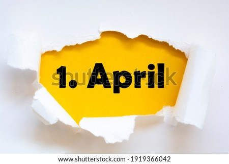 1. April (April 1st, German format) message on torn white paper revealing secret behind ripped opening. Royalty-Free Stock Photo #1919366042