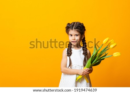 Cute little girl smiles in a yellow dress with tulips on a yellow background. Close-up. Space for text. The concept of spring. The concept of World Women's Day. March 8. The concept of spring discount