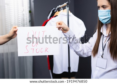 Cropped photo of two persons, business concept of empty store shelves with Out of Stock sign. Brunette woman wearing protective mask. Pandemic problems. High quality photo