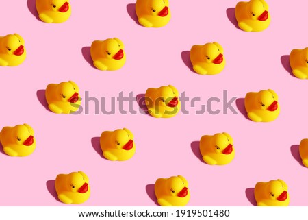 Trendy sunlight isometric view child yellow rubber duck toy background. Seamless still life seamless pattern on a pastel pink background. Minimal creative summer or kid concept.