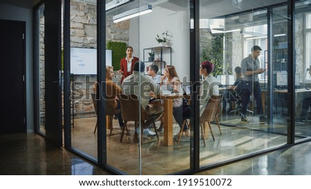 Office Conference Room Meeting: Female Chief Executive Talking to a Diverse Team of Professional Businesspeople. Creative People Listen to CEO Discuss Design, Data Analysis, Plan Marketing Strategy Royalty-Free Stock Photo #1919510072