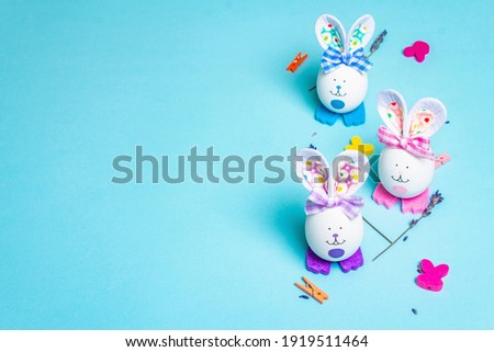 Traditional Easter symbols concept. Cute rabbits from eggs, fragrant lavender twigs, and festive decor. Pastel blue background