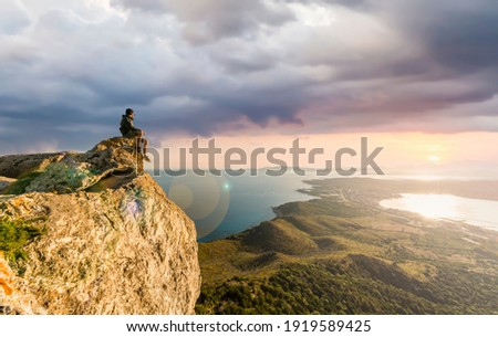 Stunning view of a boy enjoying a beautiful sunset sitting on top of a mountain, Golfo Aranci, Sardinia, Italy. Royalty-Free Stock Photo #1919589425