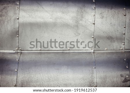 Riveted, sheet metal, waved, weathered surface abstract background image. Royalty-Free Stock Photo #1919612537