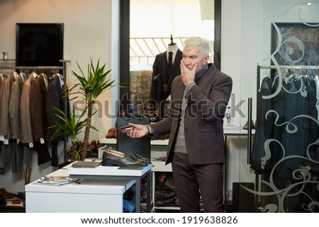 A mature man with gray hair and a sporty physique is holding a credit card to pay for purchases in a clothing store. A customer with a beard is massaging his face in a boutique